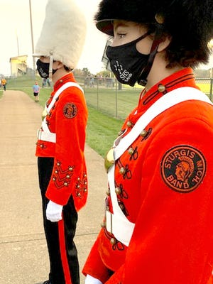 Drum majors Sophia Merchant and Ethan Klar work with the Sturgis High School marching band prior to a public performance Saturday.