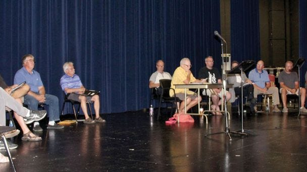 Members of the CHEDA Board of Directors and the Crookston City Council share the Crookston High School auditorium stage Tuesday evening for their joint meeting, called by Mayor Dale Stainbrook. Left to right are Betty Arvidson, Paul Eickhof, Leon Kremeier, Craig Morgan, Kurt Heldstab, Clayton Briggs, Stainbrook, Jake Fee, Don Cavalier (partially obscured), Dylane Klatt, Steve Erickson, Joe Kresl, Tom Vedbraaten and Bobby Baird.