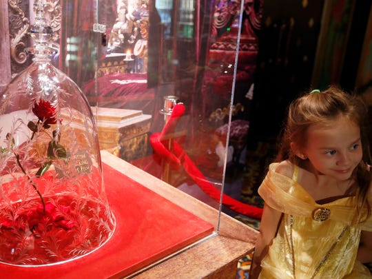 Rillie Duce, 6, poses with the rose in the lobby during the Beauty and the Beast Los Angeles premiere at the El Capitan Theatre March 16, 2017 in Hollywood, Calif.
