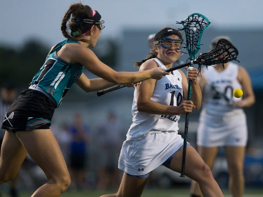 Barron Collier's Caroline Peterson (19) is checked by Gulf Coast's Lis Govern (17) as she looks to score during the first half of a first-round play-in game in the state tournament at Barron Collier High School Wednesday, April 12, 2017. Barron Collier would go on to win.