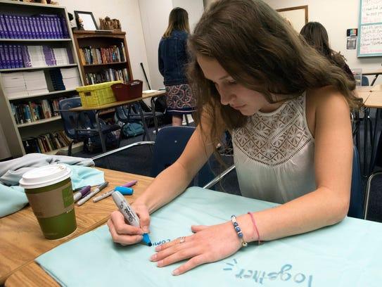 Gulf Breeze High School student Lauren Aylstock decorates