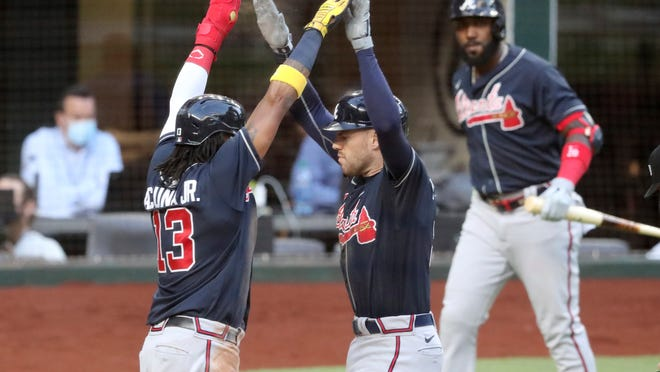 Atlanta Braves first baseman Freddie Freeman, right, celebrates his two-run home run with teammate Ronald Acuna (13) against the Los Angeles Dodgers during the fourth inning in Game 2 Tuesday, Oct. 13, 2020,  in the best-of-seven National League Championship Series at Globe Life Field in Arlington, Texas.