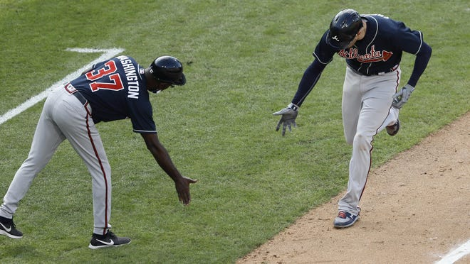 Atlanta Braves' Freddie Freeman, right, celebrates with third base coach Ron Washington after hitting a two-run home run off Philadelphia Phillies pitcher Spencer Howard during the third inning of the second baseball game in a doubleheader, Sunday, Aug. 9, 2020, in Philadelphia.