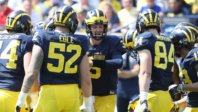 Michigan quarterback Wilton Speight, center, gathers the offense for a huddle in the spring game Saturday, April 15, 2017 at Michigan Stadium in Ann Arbor.