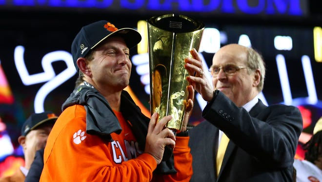 College Football Playoff Executive Director Bill Hancock presents the trophy to the Clemson Tigers head coach Dabo Swinney.