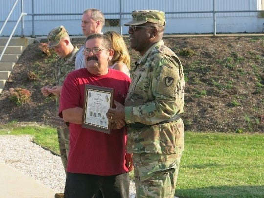 Brig. Gen. Richard Dix, Commanding General of Joint Munitions Command presents Letterkenny Munitions Center employee, Mr. David Grissinger, with a plaque during a ceremony to recognize and thank Vietnam Era Veterans