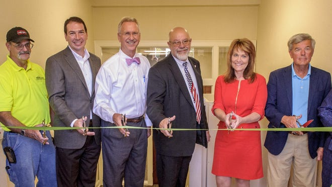 Representatives from Downing Construction, the Warren County Board of Supervisors and House of Mercy cut the ribbon at the House of Mercy's new offices in the Masonic Temple building.