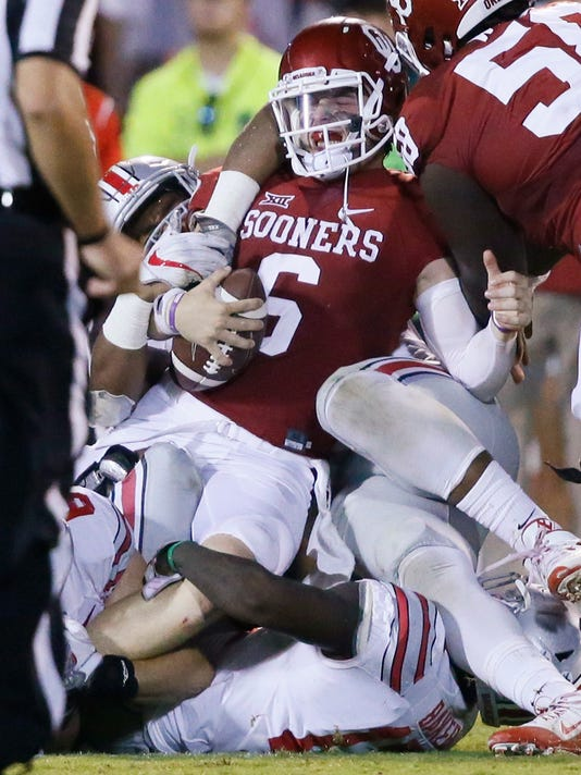 Oklahoma quarterback Baker Mayfield (6) is tackled by a number of Ohio State players during the fourth quarter an NCAA college football game in Norman, Okla., Saturday, Sept. 17, 2016. Ohio State won 45-24. (AP Photo/Sue Ogrocki)