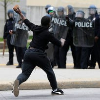 A man throws a brick at police Monday, following the funeral of Freddie Gray in Baltimore.