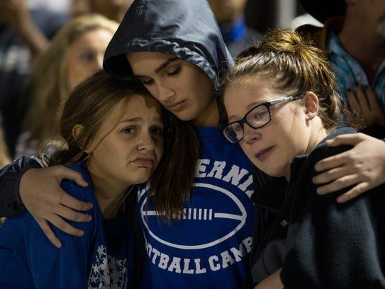 Three girls embrace during during prayer vigil for