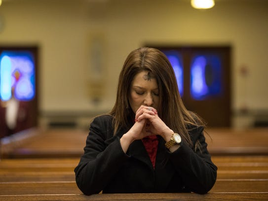 LuLu Rivera prays following a noon service at the Corpus