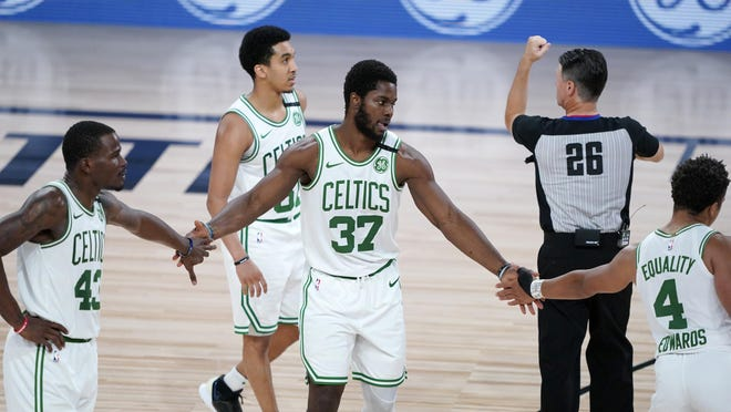 Boston's Semi Ojeleye (37) is congratulated by teammates Javonte Green and Carsen Edwards (4) during the second half of Thursday's game against the Washington Wizardsi n Lake Buena Vista, Fla. Boston will face the Sixers Monday night in their opening game of the playoffs.