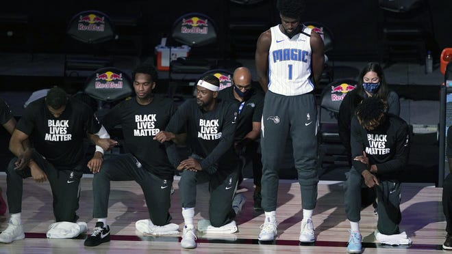 "Orlando Magic's Jonathan Isaac stands as others kneel before the start of Friday night's NBA game against the Brooklyn Nets. ""Absolutely, I believe Black lives matter,"" he said. ""I don't think kneeling and putting on a T-Shirt for me, personally, is the answer."""