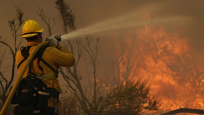 Jesse Vasquez, of the San Bernardino County Fire Dept., hoses down hot spots from the Bobcat Fire Saturday, Sept. 19, 2020, in Valyermo, Calif.