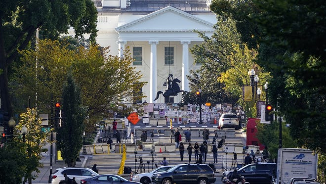 The White House is seen in Washington, early Tuesday the morning after President Donald Trump returned from the hospital where he was treated for COVID-19. Traffic moves along K Street NW as TV crews set up in Black Lives Matter Plaza.