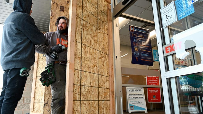 Dean Stoner, left, and Matthew Conboy install protective plywood doors over the glass doors Monday at the Aldi grocery store at 6550 E. State St., Rockford. The doors and windows were covered with plywood as a precautionary measure after two nights of looting in the city.