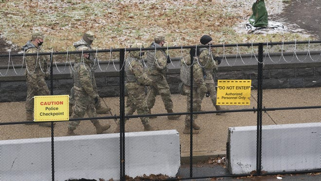 National Guard troop patrol the grounds of the Capitol in Washington, Tuesday, Jan. 26, 2021.