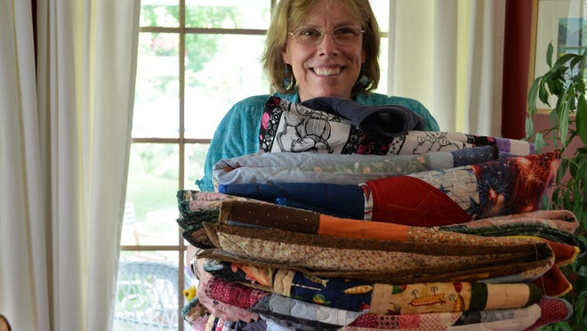 Gale Kreutz celebrate a winter's worth of work with her Island Quilters group. Fifteen members made 34 quilts for kids with cancer at Camp Ta-Kum-Ta in South Hero on June 18.