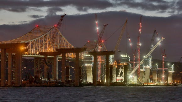 Construction cranes are lighted up for night work on the main support towers for the new Tappan Zee Bridge as as the megaproject continues. As seen from Tarrytown on Dec. 18.
