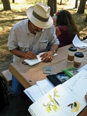 ENMU-Ruidoso students drawing in the field.