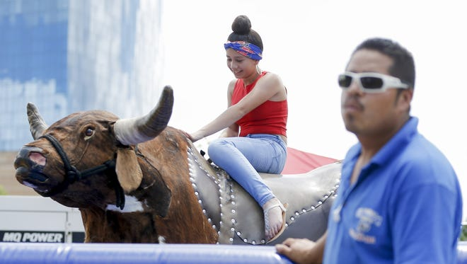 Alexandra Martinez rides the bull as Guillermo Garcia looks off into the distance during the Familia Fest at Military Park in Indianapolis on Sunday, June 24, 2018.