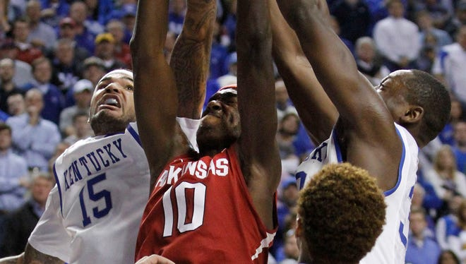 Arkansas' Bobby Portis (10) pulls down a rebound between Kentucky's Willie Cauley-Stein (15), Julius Randle and James Young (1) during the second half of an NCAA college basketball game, Thursday, Feb. 27, 2014, in Lexington, Ky. Arkansas won 71-67. (AP Photo/James Crisp)