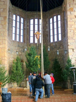 Parish members hold the poles in place.