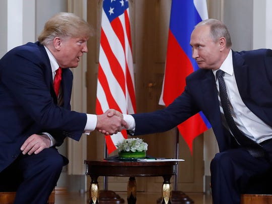 U.S. President Donald Trump, left, and Russian President Vladimir Putin, right, shake hands at the beginning of a meeting at the Presidential Palace in Helsinki, Finland, on July 16, 2018.