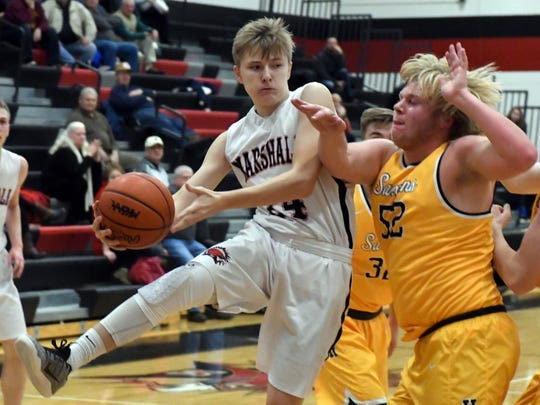 Marshall's Codey Shellenberger (24) prepares to pass under the basket during Tuesday night's matchup against Hastings.