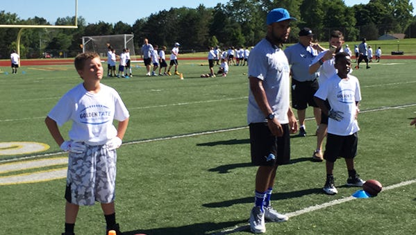 Golden Tate watches the action at his football camp on Thursday at Rochester Adams.