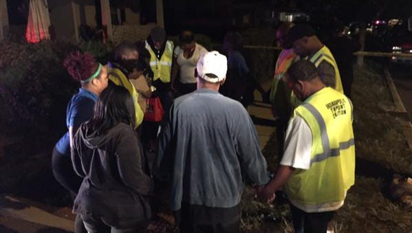 Members of Ten Point Coalition pray with family members of victims at the scene of a quadruple shooting  on the Northside that left a child dead Saturday, Sept. 19, 2015.