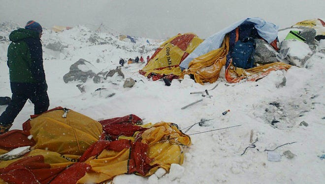 In this photo provided by Azim Afif, shows a man approaching the scene after an avalanche triggered by a massive earthquake swept across Everest Base Camp, Nepal.