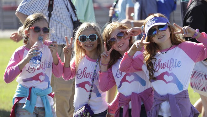 Taylor Swift fans, from left, Brie Bauman, Avery Frollo, Lynleigh Schulte and Kambrie Schulte pose for a photo as they walk around the Circuit of the Americas track while they wait for a concert to begin Saturday after qualifications for the Formula One U.S. Grand Prix.
