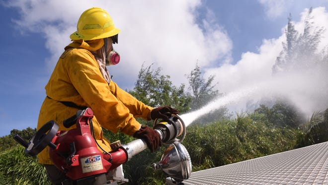 In this Jan. 22, 2018, file photo, a Guam Fire Department firefighter uses a vehicle-mounted water cannon to saturate grassland along Route 17, also known as Cross Island Road, in Santa Rita. Traffic was temporarily closed on the roadway as GFD, Department of Agriculture's Forestry Division and the U.S. Navy Emergency Services firefighters battled a wildfire that threatened homes in the area.