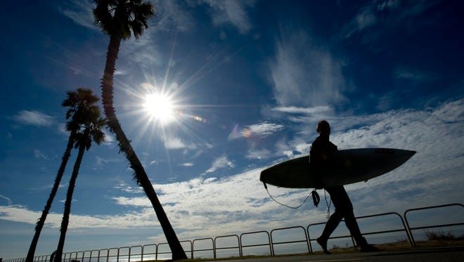 Steve Farnsworth heads back to his car after a morning of surf near Dog Beach in Huntington Beach, Calif., Tuesday, Dec. 17, 2013.