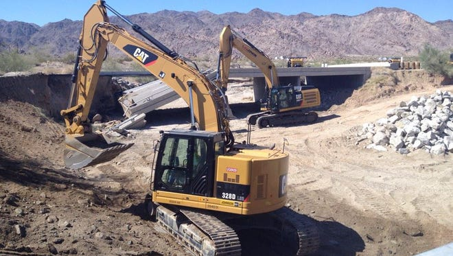 Two  excavators  work on the wash on Wednesday, July 22, where a Interstate 10 bridge collapsed in California,