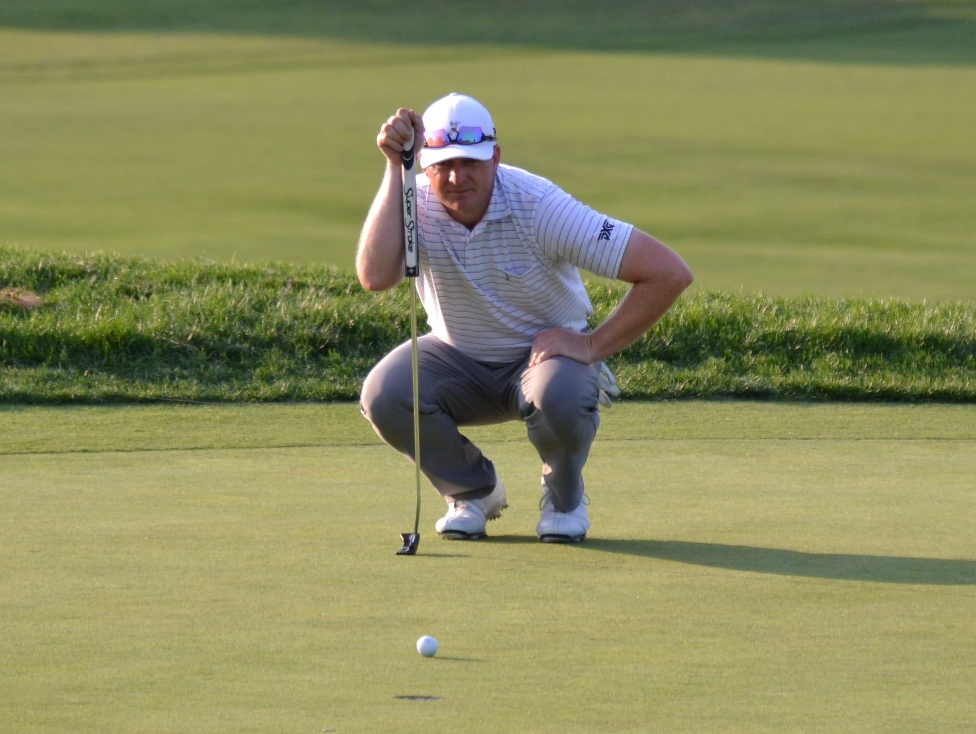Winged Foot assistant Grant Sturgeon takes a quick look at a bogey putt on the 18th green of the Black Course at Bethpage State Park. He shot a 75 in the second round of the state open Wednesday and is tied for 21st.