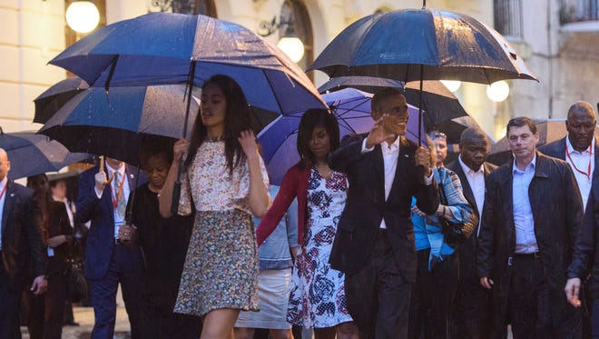 President Obama (right), First lady Michelle Obama, and their daughter Malia Obama (left) walk in the heavy rain visiting Cathedral Square in Havana on Sunday.