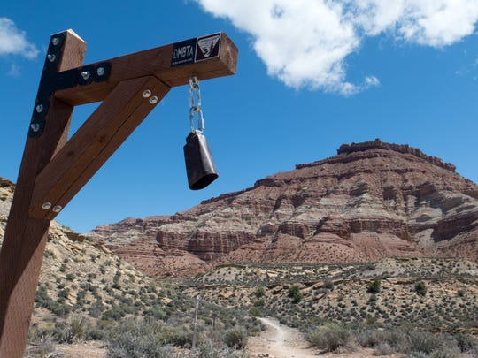 A cowbell hangs from a post at the intersection of the Dead Ringer and More Cowbell trails in the Hurricane Cliffs Trail System Thursday, April 16, 2015.