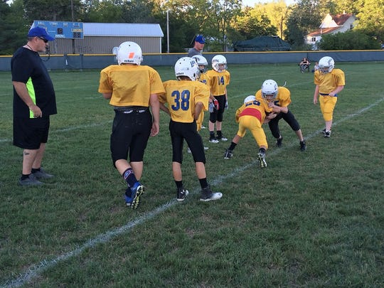 """Assistant coach Chuck Crandall, left, and head coach Casey Crandall monitor a tackling drill during practice Monday evening. All 12 Small Fry football coaches are certified to teach """"Heads-Up Football,"""" a program that helps players learn to play safely."""