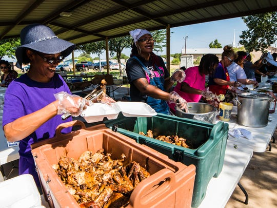 An assembly line of volunteers fills plates for hungry