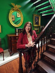 "Linda Danko is shown with Delaware's first fireproof stair – an 1850s cast-iron starcase that is original to the Bigg Museum's interior. ""We took every square inch and turned it into usable gallery space,"" she says."