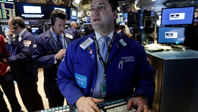 Specialist Ronnie Howard, right, works at his post on the floor of the New York Stock Exchange Monday, Feb. 23, 2015. U.S. stocks are opening slightly lower, pulling the market back from an all-time high reached last week.