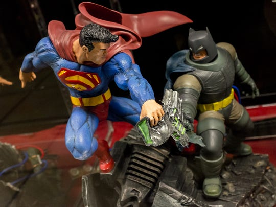 Large figurines of Superman and Batman battle it out