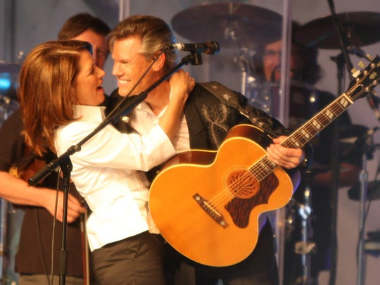 Michele Bachmann hugs country singer Randy Travis in her tent at the straw poll in Ames in 2011.
