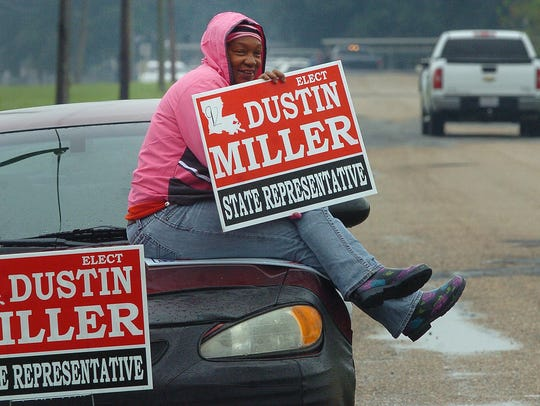 A campaign worker waves at passing motorist Saturday