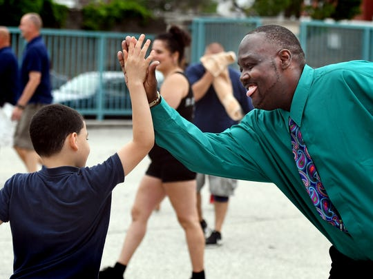 Lincoln Charter School principal Leonard Hart high-fives a student during the Community Kickball game at the school Tuesday, May 29, 2018. The contest was part of a week-long series of fundraisers to benefit the American Cancer Society. All players--parents, teachers, emergency responders and students--paid a $5 fee to play in the game which pitted the adults against the school's fifth graders. Bill Kalina photo