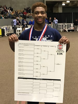 Sycamore's Tyree Bass holds up a bracket showing his state title.