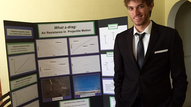 "Sawyer, a junior, with his last tri-fold display board, ""What a draf: Air resistance in projectile motion."""