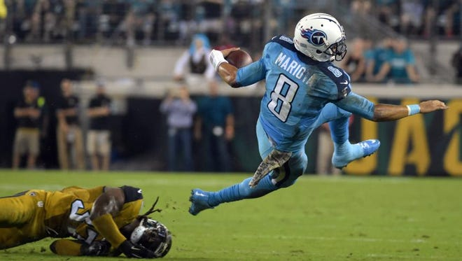 Titans quarterback Marcus Mariota (8) is tackled by Jaguars strong safety Johnathan Cyprien (37).